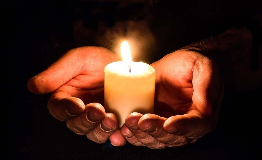 Cupped hands together in the dark holding a lit candle