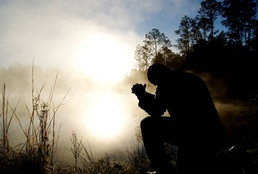 Man seated by edge of lake praying at breaking of dawn